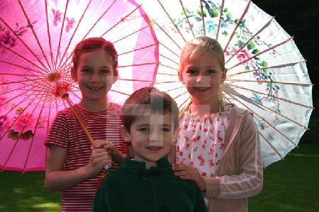 drei Kinder unter Schirmen