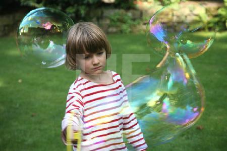 Junge in Ringelshirt mit Seifenblase