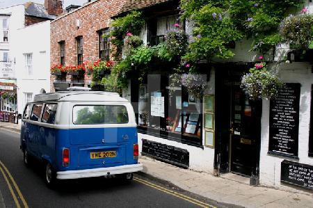Straße mit blauem VW-Bus in Rye, Südengland